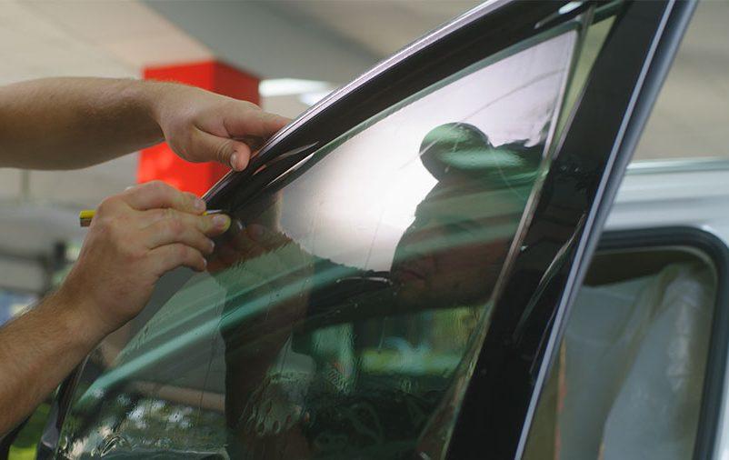 Vemos um homem tendo cuidados com carro blindado.